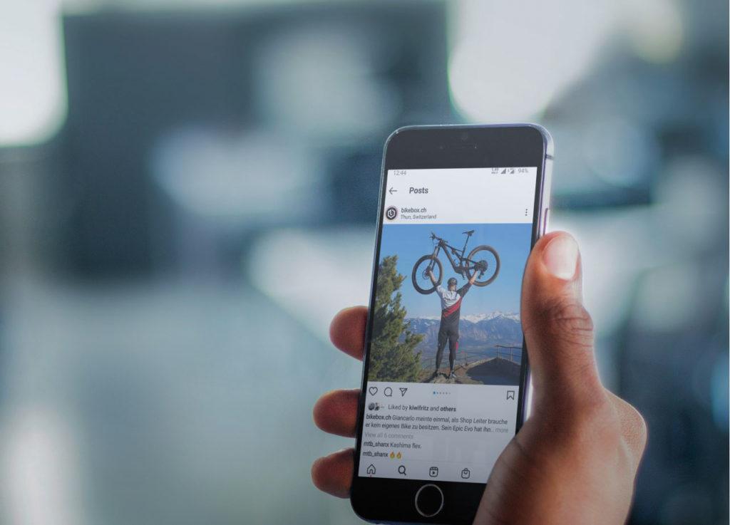 Hand mit Smartphone, auf dem ein Instagram Post mit einem Mountainbiker gezeigt wird.